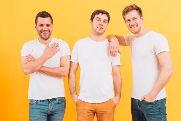 Portret van glimlachende drie mannelijke vrienden die in witte t-shirt camera bekijken Gratis Foto