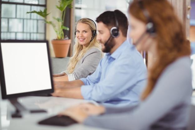 Portret van glimlachende exploitant met collega's in bureau Premium Foto