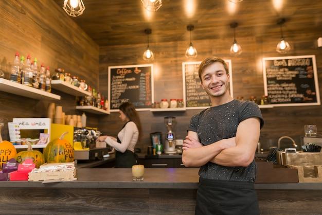 Portret van glimlachende jonge mannelijke coffeeshophouder Premium Foto