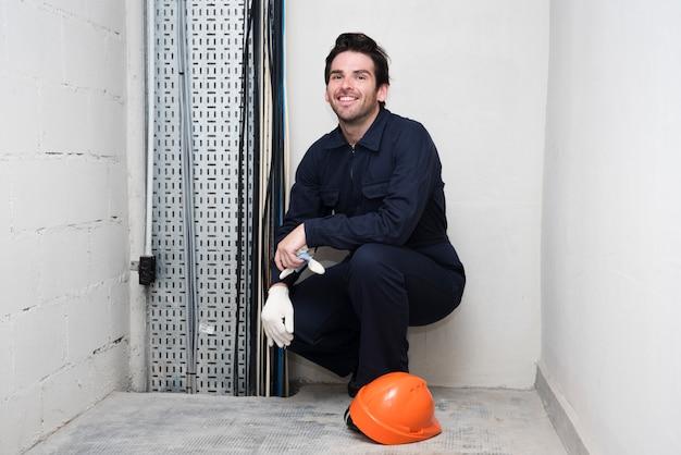 Portret van glimlachende jonge mannelijke elektricien op het werk Gratis Foto