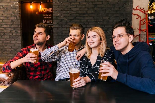 Portret van glimlachende jonge vrienden die van het bier genieten Gratis Foto
