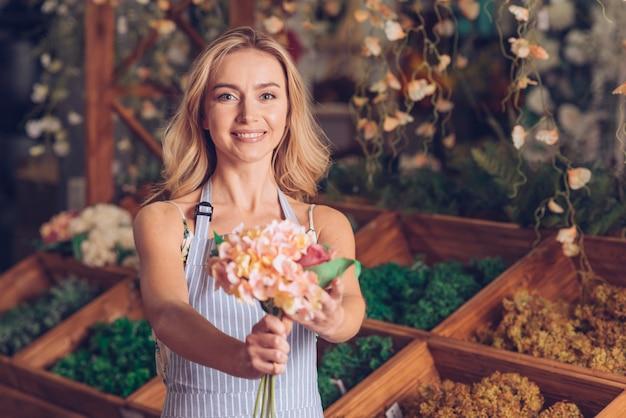 Portret van glimlachende jonge vrouwelijke bloemist die de bloemen aanbieden Gratis Foto