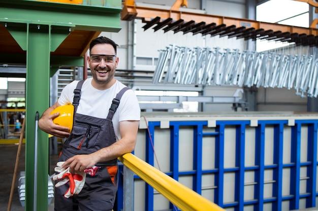 Portret van glimlachende man fabrieksarbeider permanent in industriële productiehal Gratis Foto