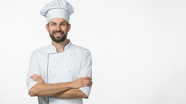 Portret van glimlachende mannelijke chef-kok in witte die eenvormig over witte achtergrond wordt geïsoleerd Gratis Foto