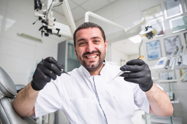 Portret van glimlachende mannelijke tandarts met tandhulpmiddelen Gratis Foto