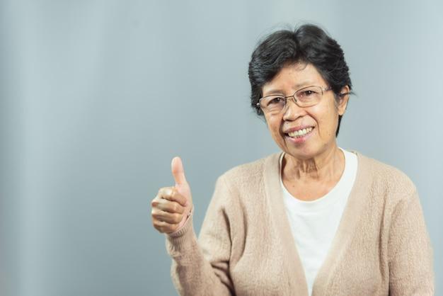 Portret van glimlachende oude vrouw op grijs Premium Foto