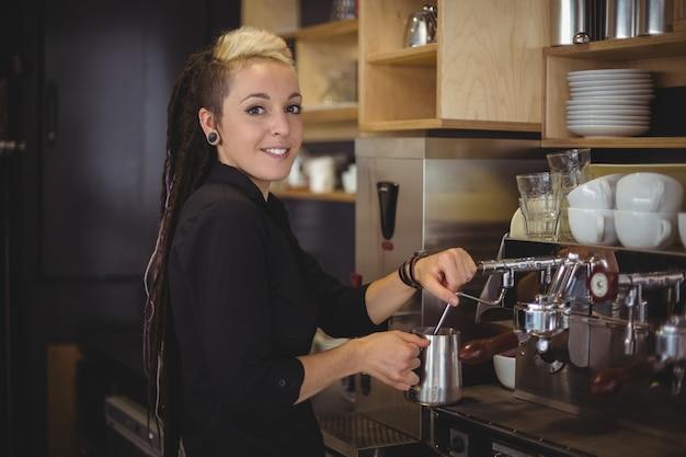 Portret van glimlachende serveerster die de koffiemachine met behulp van Gratis Foto