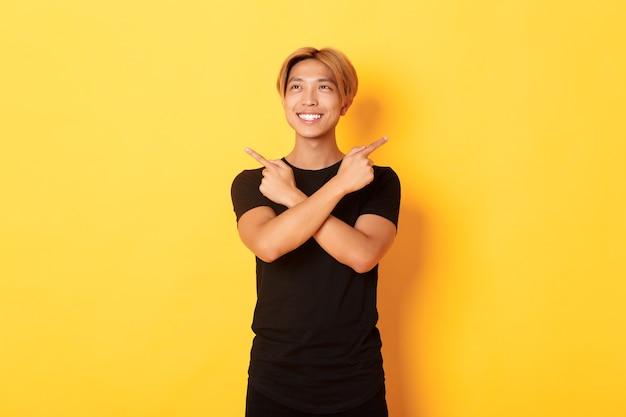 Portret van glimlachende tevreden aziatische kerel, die naar links kijkt en besluit, zijwaarts richt, gele muur Gratis Foto