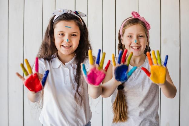 Portret van glimlachende twee meisjes die kleurrijke geschilderde handen tonen die aan camera kijken Gratis Foto