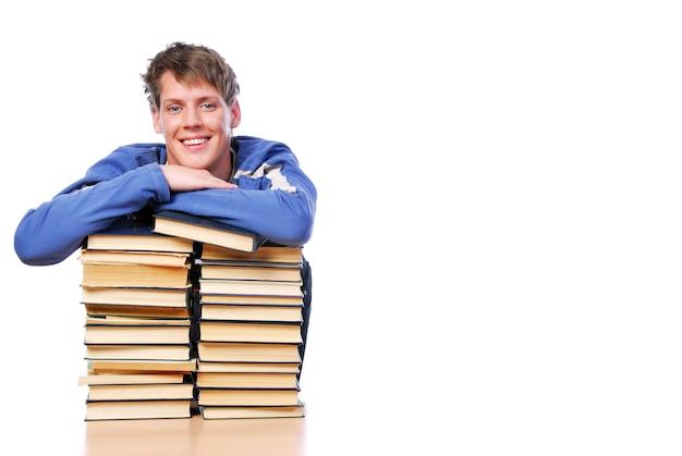 Portret van glimlachende volwassen jonge slimme man in een dagboek op de stapel boeken Gratis Foto