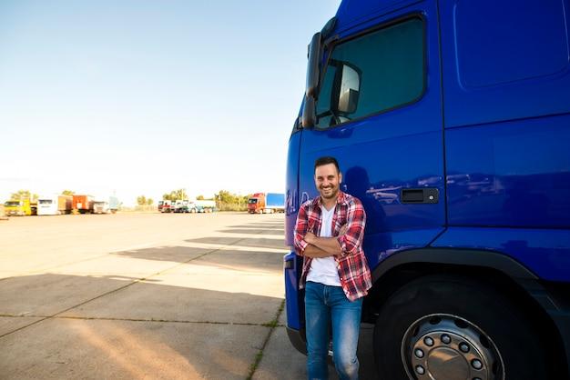 Portret van glimlachende vrachtwagenchauffeur die zich door zijn vrachtwagen bevindt die klaar is om te rijden Gratis Foto