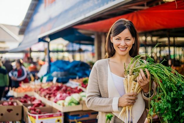 Portret van glimlachende vrouw bij groene markt het kopen groenten. Premium Foto