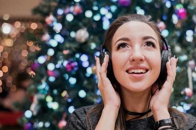 Portret van glimlachende vrouw die hoofdtelefoons draagt dichtbij kerstmisboom Gratis Foto