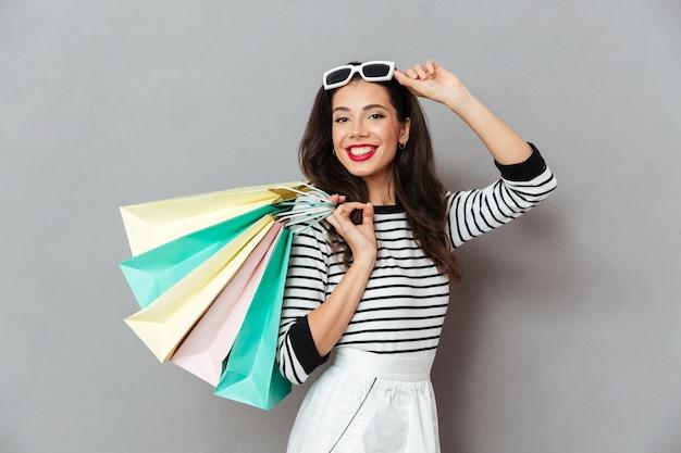 Portret van glimlachende vrouwenholding het winkelen zakken Gratis Foto