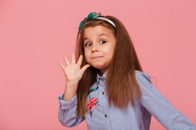 Portret van grappig vrouwelijk jong geitje dat lang kastanjebruin haar heeft kijkend hoog vijf die hallo of tot ziens met hand betekenen Gratis Foto