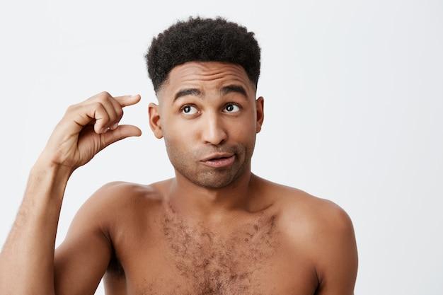 Portret van grappige donkere amerikaanse man met krullend haar en zonder kleren opzij kijken met gekke en cynische uitdrukking, gebarend met de hand. emoties van mensen. Gratis Foto