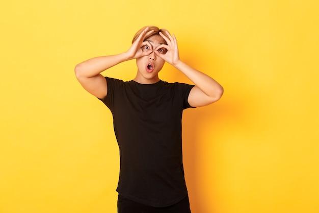 Portret van grappige en schattige aziatische blonde kerel die vingers glazen en grimassen, staande gele muur maakt Gratis Foto
