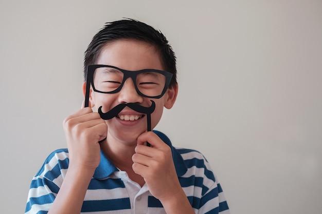 Portret van grappige gemengde aziatische jongen die pret met valse snor hebben Premium Foto