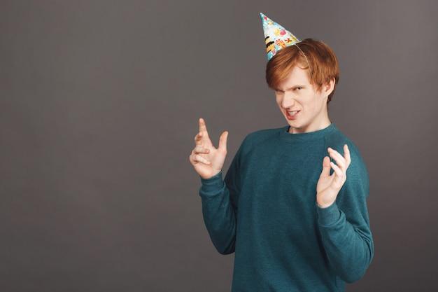 Portret van grappige jonge roodharige man in groene trui en feestmuts verspreiden handen met walging expressie Gratis Foto