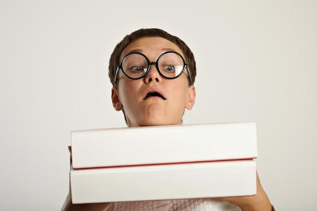 Portret van grappige studente die twee zware grote mappen met educatieve planningsdocumenten voor haar houdt Gratis Foto