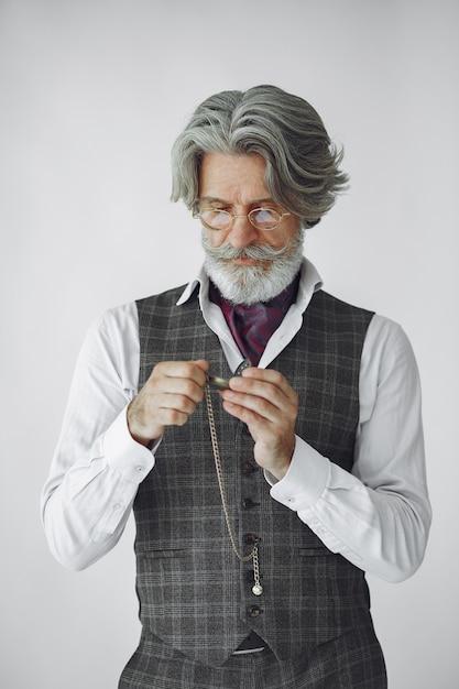 Portret van grijnzende ouderwetse man close-up. grootvader met een klok. Gratis Foto