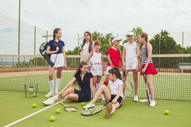 Portret van groep meisjes als tennisspelers die tennisrackets houden tegen groen gras van openluchthof. Gratis Foto