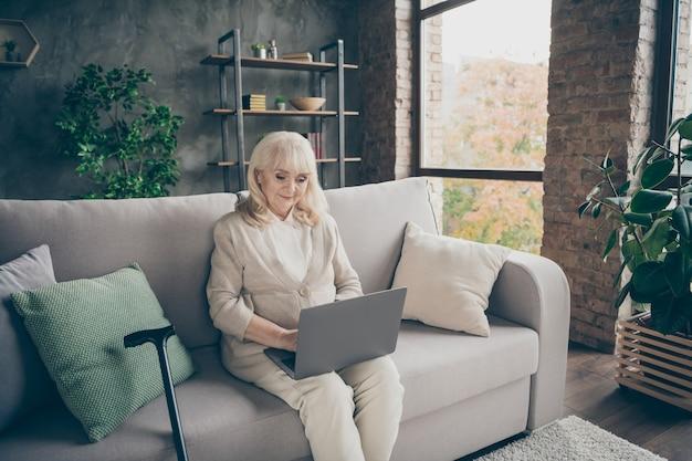Portret van haar ze mooie aantrekkelijke rustige vriendelijke grijsharige dame zittend op een divan schrijven e-mail chatten zoeken website op industriële bakstenen loft moderne stijl interieur huis binnenshuis Premium Foto