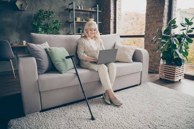Portret van haar ze mooie aantrekkelijke vriendelijke vreedzame vriendelijke grijsharige dame zittend op een divan e-mail verzenden naar familieleden uitnodigend voor een bezoek aan industriële bakstenen loft moderne stijl interieur huis binnenshuis Premium Foto