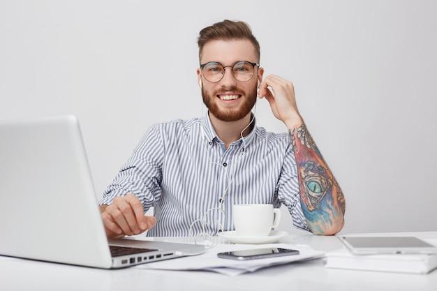 Portret van heerlijke tevreden bebaarde man met trendy kapsel luistert naar audiotrack met koptelefoon Gratis Foto