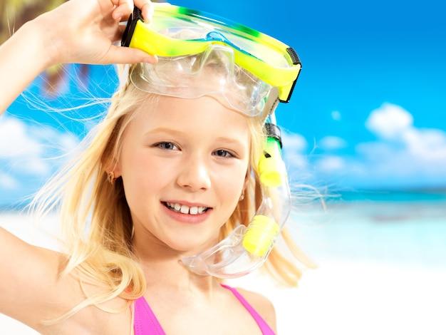 Portret van het gelukkige meisje die bij strand genieten van. schoolkind meisje met zwemmend masker op hoofd. Gratis Foto