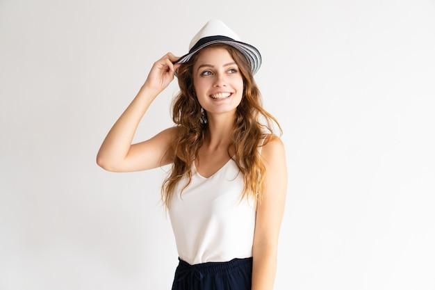Portret van het gelukkige modieuze jonge vrouw stellen in hoed. Gratis Foto
