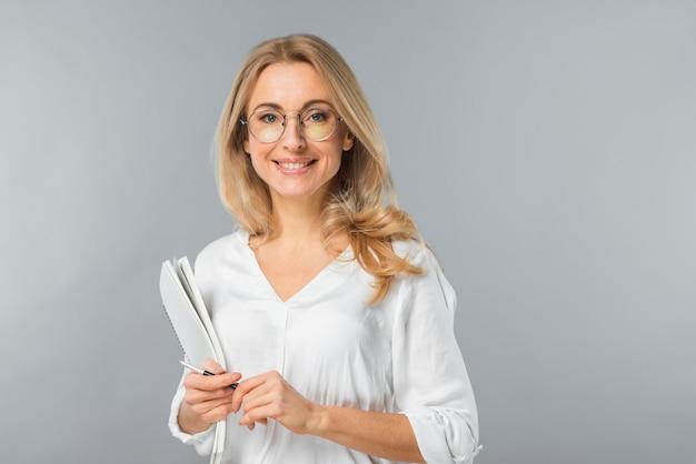 Portret van het glimlachen van de holdingsdocument en pen van de blonde jonge onderneemster tegen grijze achtergrond Gratis Foto