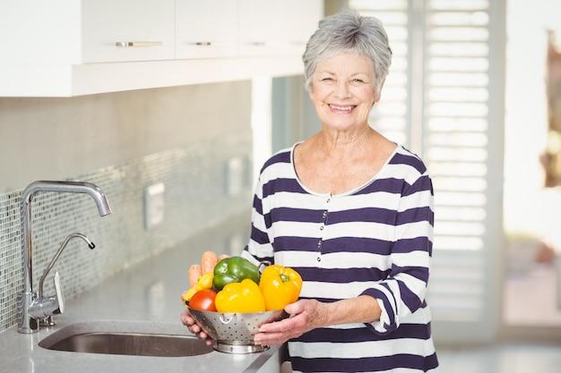 Portret van het hogere vergiet van de vrouwenholding met groenten Premium Foto