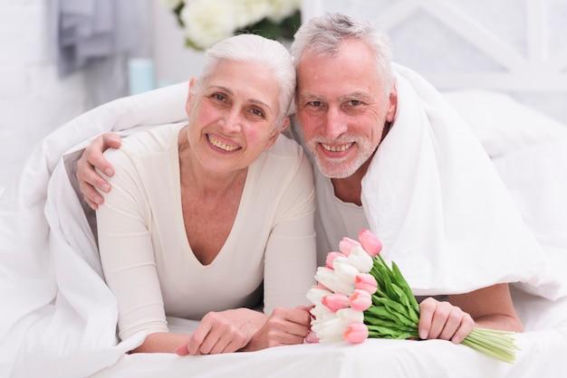 Portret van het houden van van ouder paar die op bed met mooi bloemboeket liggen Gratis Foto