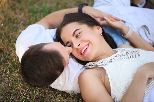 Portret van het jonge aanbiddelijke paar in liefde die hoofd aan kop in openlucht liggen Premium Foto