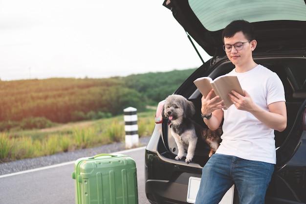 Portret van het jonge aziatische boek van de mensenlezing terwijl het zitten in auto open boomstam met zijn honden. Premium Foto
