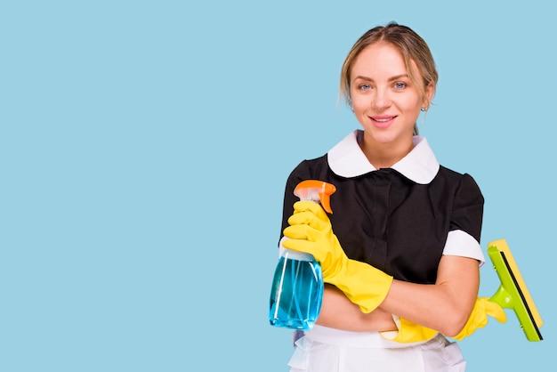 Portret van het jonge mooie schoonmakende materiaal die van de vrouwenholding camera bekijken Gratis Foto