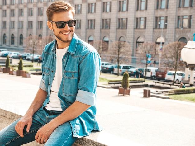 Portret van het knappe het glimlachen modieuze model van hipster lumbersexual zakenman. de mens kleedde zich in de kleren van het jeansjasje. Gratis Foto