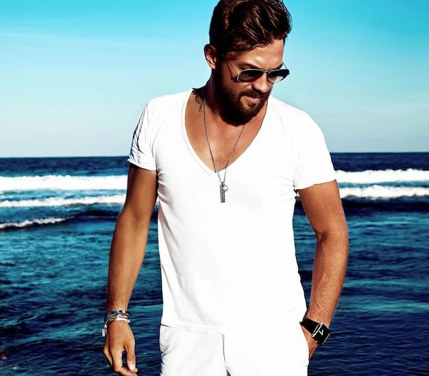 Portret van het knappe model die van de maniermens witte kleren dragen die op blauwe overzees stellen Gratis Foto