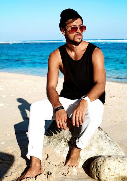 Portret van het knappe model van de hipster zonnebaden maniermens die vrijetijdskleding in zwarte t-shirt dragen en zonnebril die op rotsen zitten Gratis Foto