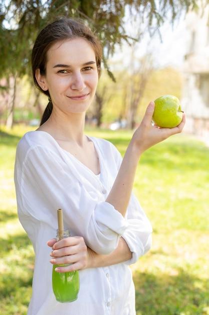 Portret van het sapfles en appel van de vrouwenholding Gratis Foto