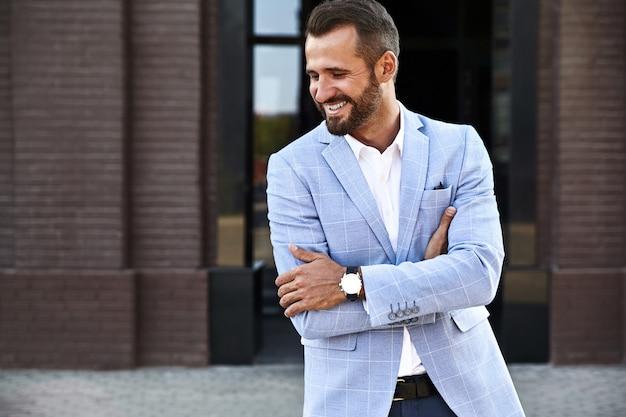 Portret van het sexy knappe model van de manierzakenman gekleed in het elegante blauwe kostuum stellen op straatachtergrond. metrosexual Gratis Foto