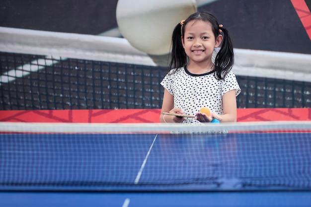 Portret van het spelpingpong van het glimlach aziatisch meisje Premium Foto