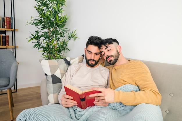 Portret van het vrolijke paar ontspannen samen op bank terwijl het lezen van het boek Gratis Foto