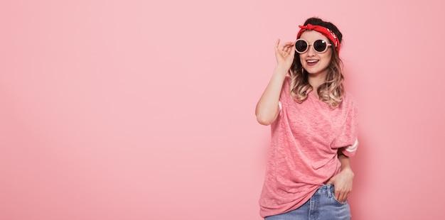Portret van hipster meisje in glazen op roze muur Gratis Foto