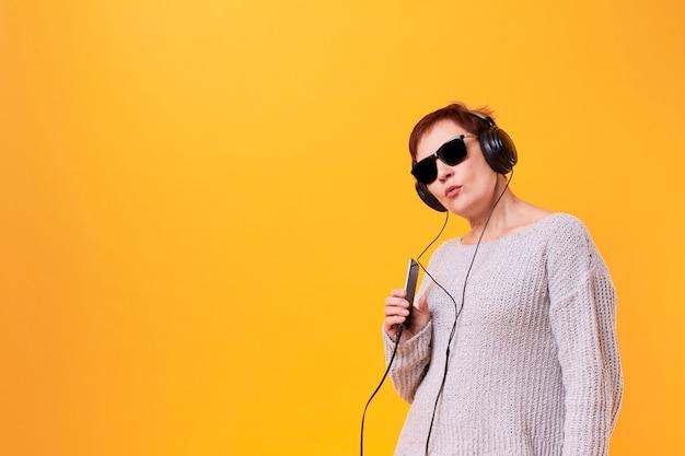 Portret van hogere vrouw het luisteren muziek met exemplaarruimte Gratis Foto