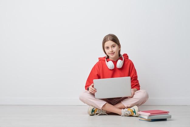 Portret van inhoud moderne middelbare school meisje in rode hoodie zittend met gekruiste benen op de vloer en met behulp van draagbare computer Premium Foto