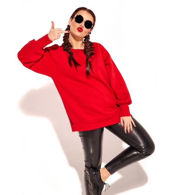 Portret van jong gelukkig het glimlachen vrouwenmodel met heldere make-up en kleurrijke lippen met twee geïsoleerde vlechten en zonnebril in de zomer rode kleren. fuck off teken tonen Gratis Foto