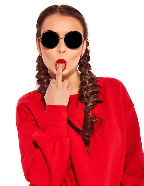 Portret van jong gelukkig het glimlachen vrouwenmodel met heldere make-up en kleurrijke lippen met twee geïsoleerde vlechten en zonnebril in de zomer rode kleren. middelvinger likken, rot op teken Gratis Foto