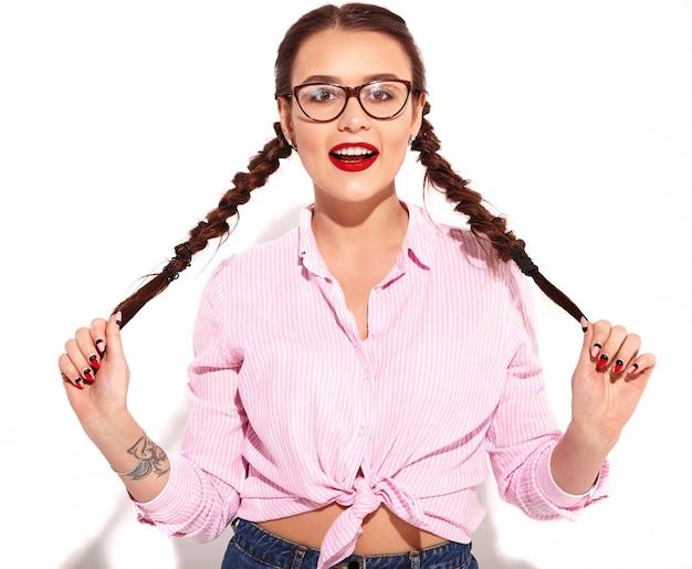 Portret van jong gelukkig het glimlachen vrouwenmodel met heldere make-up en rode lippen met twee geïsoleerde vlechten in geïsoleerd zomer kleurrijk roze gebonden overhemd Gratis Foto
